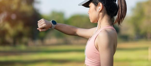 公園の屋外でのランニング中にスポーツスマートウォッチで時間とカーディオ心拍数をチェックする若い大人の女性、朝ジョギングしているランナーの女性。運動、テクノロジー、ライフスタイル、トレーニング