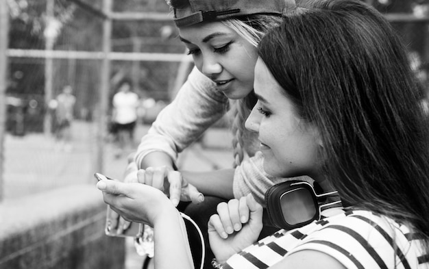 Молодых взрослых женщин-друзей, слушать музыку через смартфон на открытом воздухе