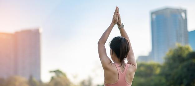 Молодая взрослая женщина в розовой спортивной одежде, растягивая мышцы в парке на открытом воздухе.