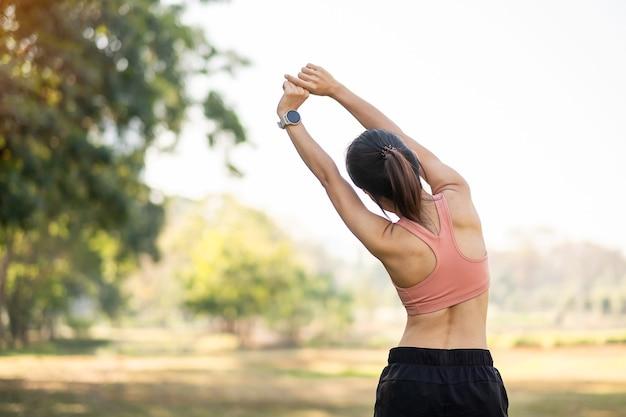 屋外の公園で筋肉を伸ばすピンクのスポーツウェアの若い大人の女性。