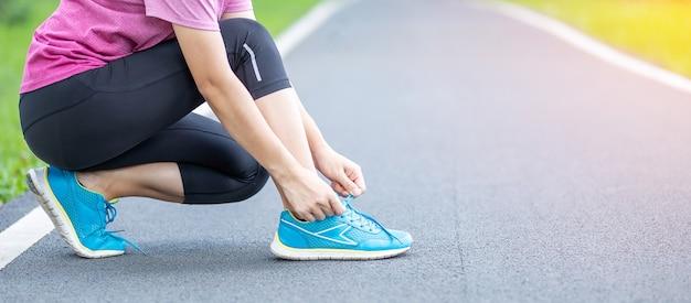 야외 공원에서 신발 끈을 묶는 운동복에 젊은 성인 여성