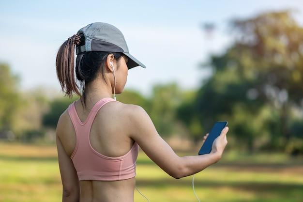 若い大人の女性は、屋外の公園で走っている間、スマートフォンで音楽を聴きます。