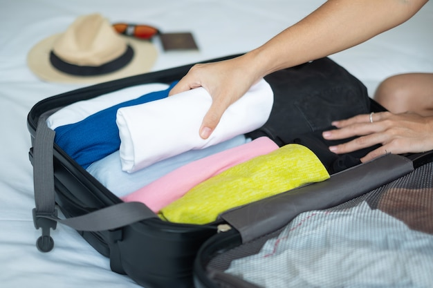 Young adult female packing luggage for summer vacation. woman tourist checking list travel accessories in suitcase on the bed. time to travel, relaxation, journey, trip and weekend concepts