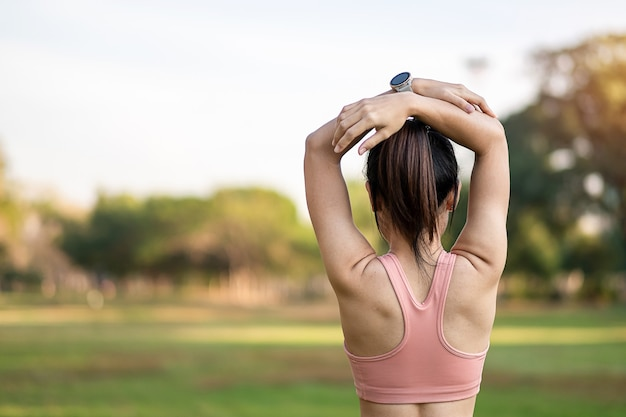 Young adult female in pink sportswear stretching muscle in the park outdoor.