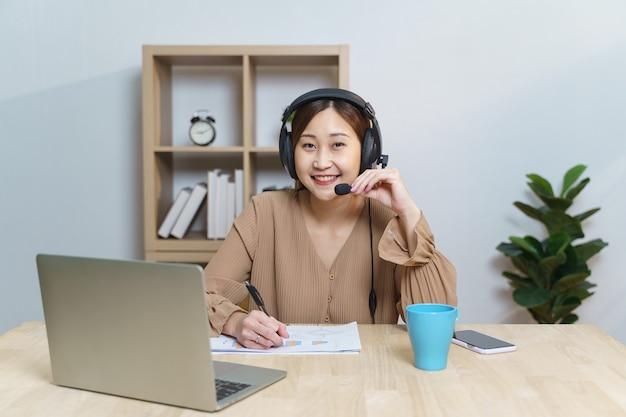 젊은 성인 여성은 거실에 앉아 컴퓨터 공부를 하고 아파트에서 배우는 헤드셋을 착용합니다. 홈 오피스에서 프리랜서로 일하는 사업가