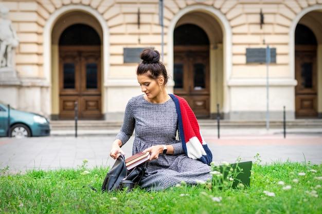 若い大人の女子学生は大学の建物の近くの草の上に座ってバックパックに本を置きます