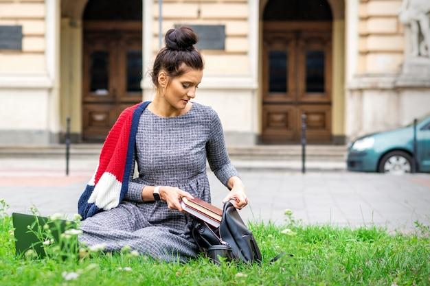 Молодая взрослая студентка кладет книги в рюкзак, сидя на траве возле здания университета