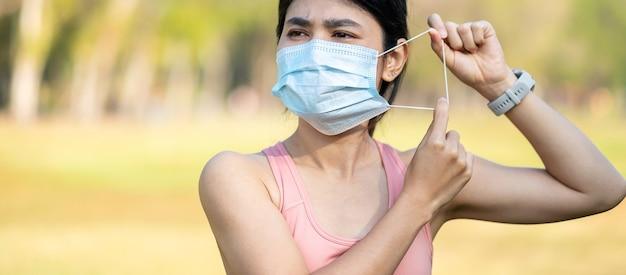 Молодая взрослая женщина в защитной маске во время растяжки мышц в парке на открытом воздухе