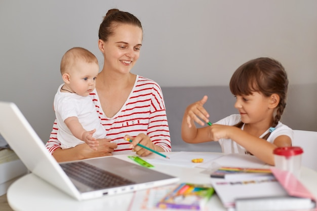Young adult female wearing striped shirt holding baby in hands and helping her elder daughter to do homework, spending time together, having happy positive expression.