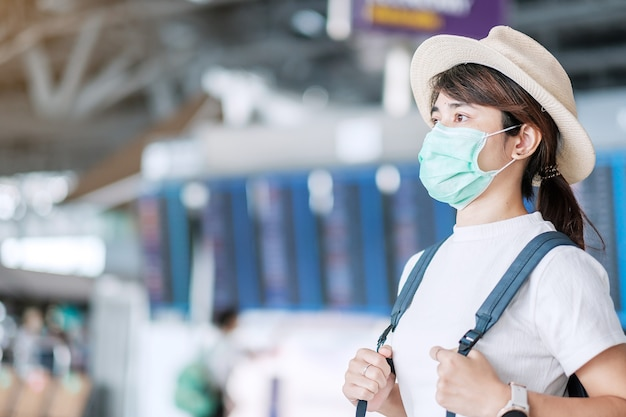 공항 터미널, 보호 코로나 바이러스 질병 (covid-19) 감염, 여행 준비가 모자와 함께 아시아 여성 여행자에 수술 마스크를 착용하는 젊은 성인 여성. 새로운 일반 및 여행 거품 개념