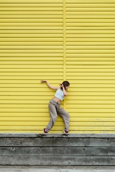 Young adult female in white top and grey pants dancing in front of bright yellow wall