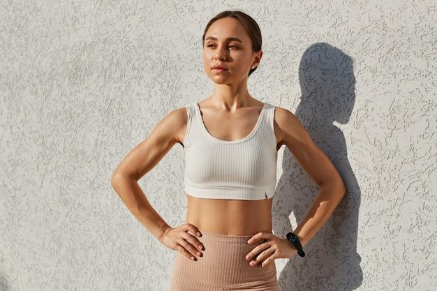 屋外の壁の近くに立って、目をそらし、腰に手を置いて、白いスポーティなトップを身に着けている黒髪の若い大人の女性は、自信を持って表情を持っており、トレーニング後にポーズをとっています。