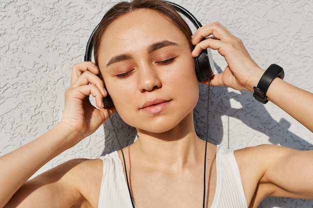 Young adult female with dark hair wearing white top, keeping eyes closed, touching headphones with palms, enjoying music after work out, healthy lifestyle.