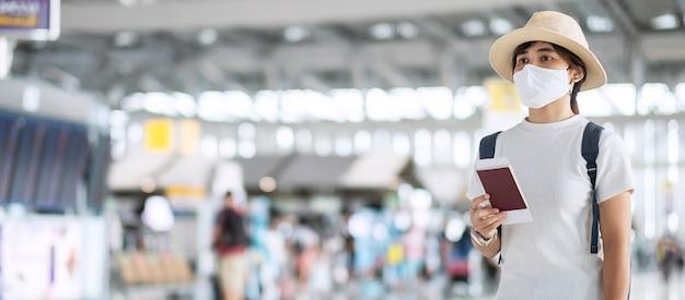 空港ターミナルでパスポートを保持しているフェイスマスクを持つ若い大人の女性