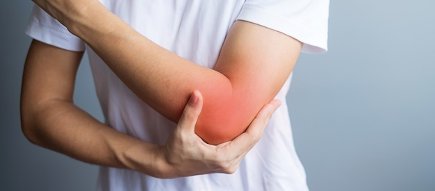 Young adult female with her muscle pain on gray background. woman having elbow ache due to lateral epicondylitis or tennis elbow. injuries and medical concept