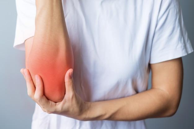 灰色の背景に彼女の筋肉痛を持つ若い大人の女性。外側上顆炎またはテニス肘が原因で肘が痛む女性。怪我と医療の概念