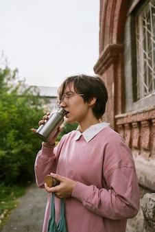 Молодая взрослая женщина с короткими волосами пьет из металла устойчивую воду на открытом воздухе