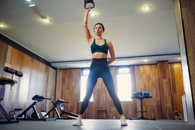 ケトルベルでスイング運動をしている若い大人のフィットネス女性
