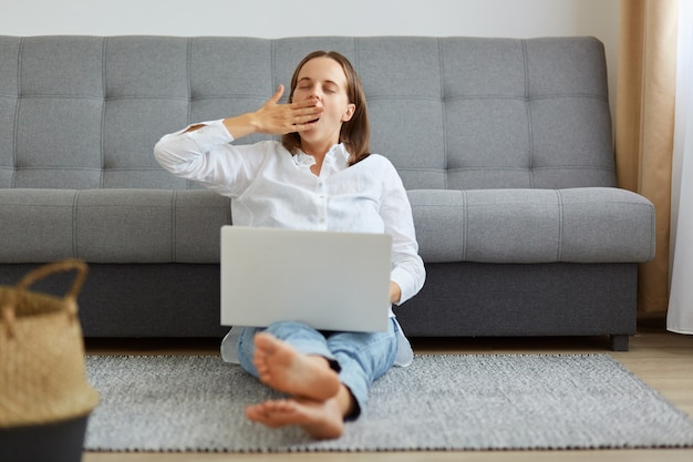Young adult freelancer woman yawning while sitting on the floor in front of laptop, covering her mouth out of courtesy, drowsiness, unable to deal with boring job.