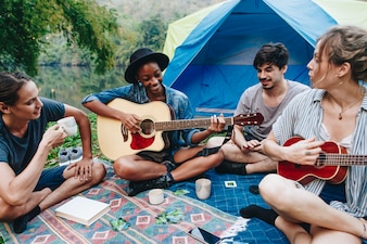Young adult friends in camp site playing guitar and ukelele and singing together outdoors