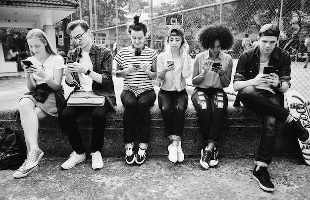 Young adult friends using smartphones together outdoors youth culture concept
