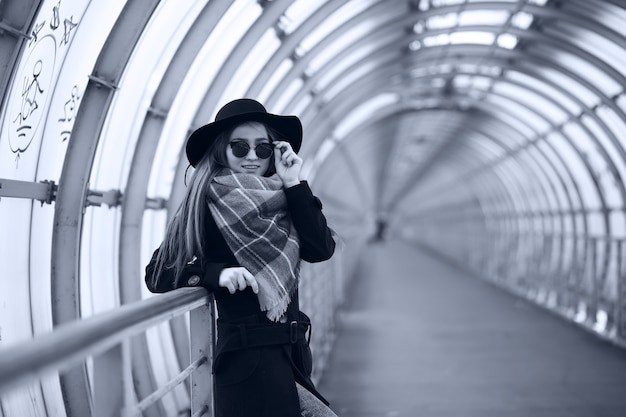 Young adult girl in the architectural tunnel of the bridge