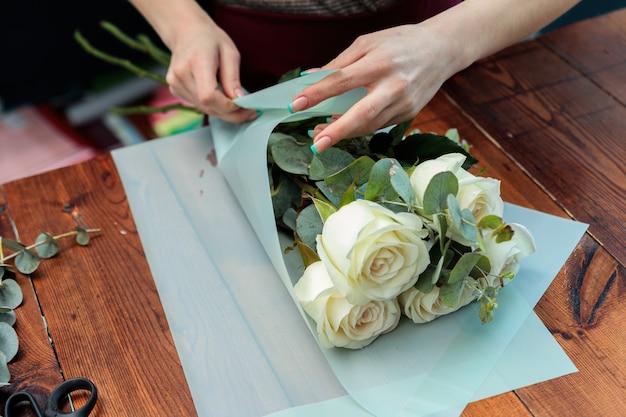 Флорист молодой взрослой девушки делает букет белых роз. фото крупным планом.