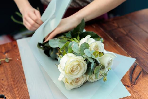 젊은 성인 소녀 꽃집은 흰 장미 꽃다발을 만듭니다. 근접 사진입니다.