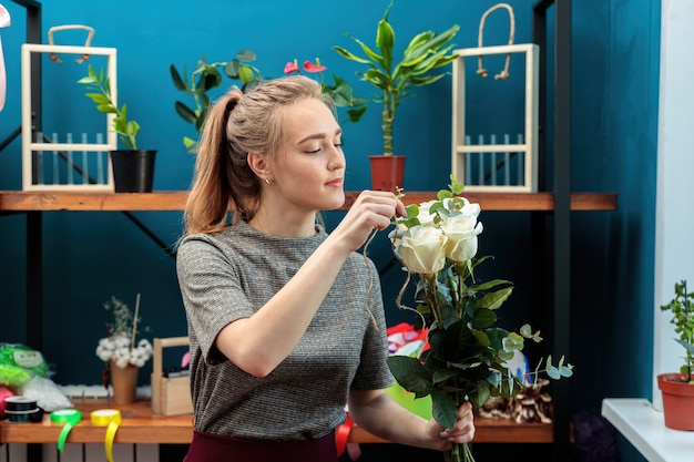 Флорист молодой взрослой девушки делает букет белых роз.