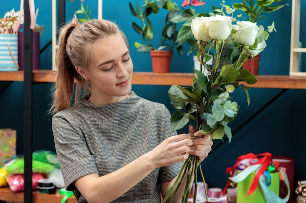 Young adult girl florist makes a bouquet of white roses.