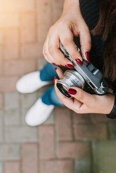 Молодая взрослая девушка держит винтажную камеру на открытом воздухе