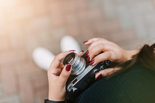 屋外でビンテージカメラを保持している若い大人の女の子