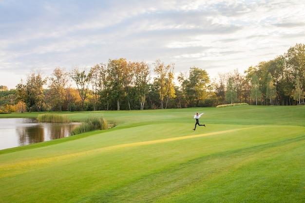 若い大人の女の子は、ゴルフコースの緑の芝生の上を走ります。女の子の幸せ。アウトドアショット、秋
