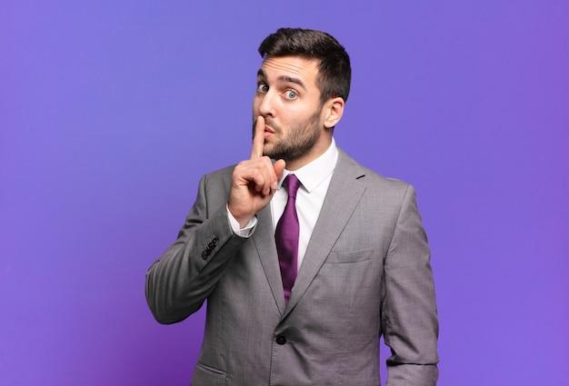 침묵과 조용함을 요구하는 젊은 성인 잘 생긴 사업가, 입 앞에서 손가락으로 몸짓, 쉿 말 또는 비밀 유지