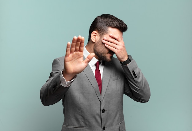 Young adult handsome businessman covering face with hand and putting other hand up front to stop camera, refusing photos or pictures