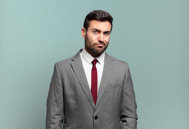 Молодой взрослый красивый бизнесмен, чувствуя себя смущенным и сомнительным, задаваясь вопросом или пытаясь выбрать или принять решение