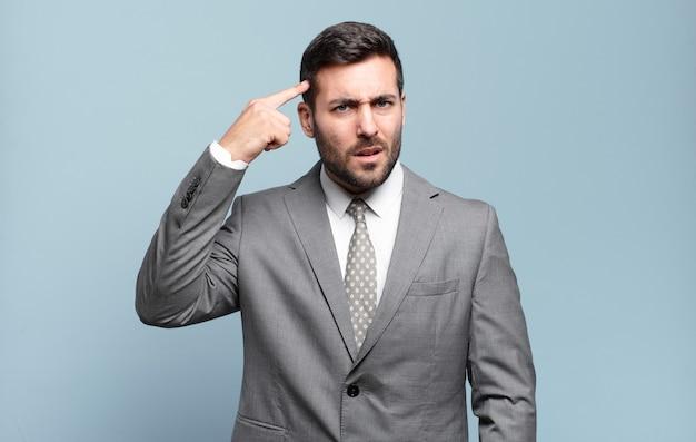 Молодой взрослый красивый бизнесмен смущен и озадачен, показывая, что вы сошли с ума, сошли с ума или сошли с ума