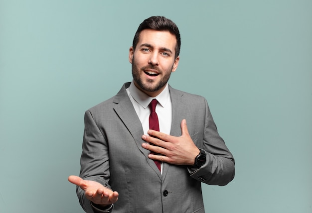 Young adult handsome businessman feeling happy and in love, smiling with one hand next to heart and the other stretched up front