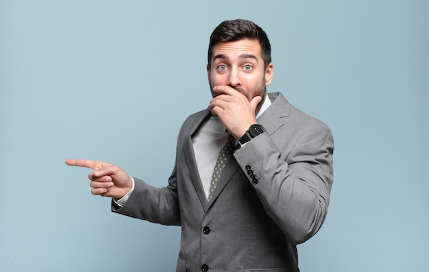 Young adult handsome businessman feeling happy, shocked and surprised, covering mouth with hand and pointing to lateral copy space