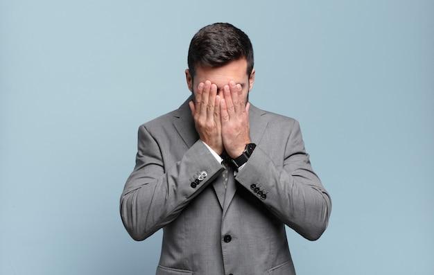Молодой взрослый красивый бизнесмен чувствует грусть, разочарование, нервозность и депрессию, закрывая лицо обеими руками, плачет