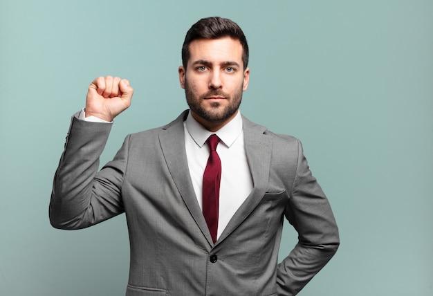 真面目で、強く、反抗的で、拳を上げ、抗議し、革命のために戦う若い大人のハンサムなビジネスマン