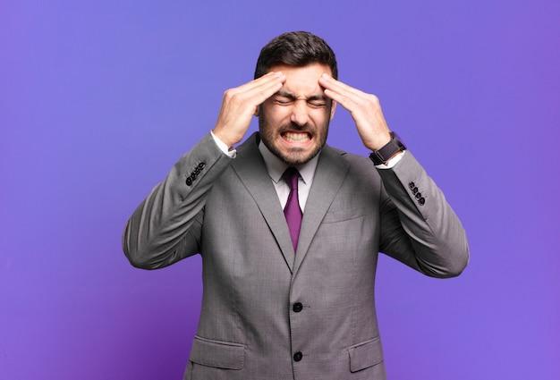 若い大人のハンサムなビジネスマンは、ストレスと不安を感じ、頭痛で落ち込んで欲求不満を感じ、両手を頭に上げます