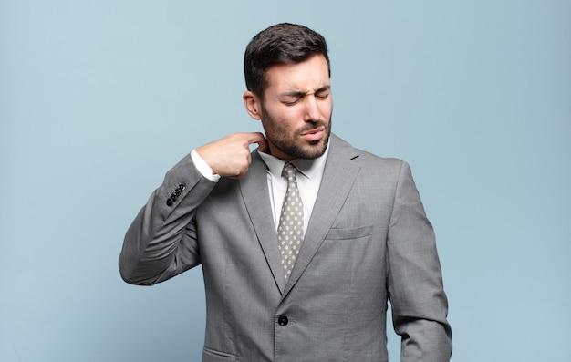 Молодой взрослый красивый бизнесмен чувствует стресс, тревогу, усталость и разочарование, дергает за шею рубашки, выглядит разочарованным из-за проблемы