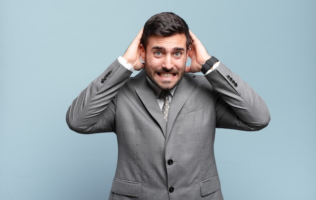 若い大人のハンサムなビジネスマンは、頭に手を置いて、ストレス、心配、不安、または恐怖を感じ、誤ってパニックに陥る
