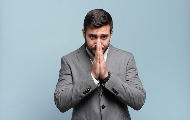 Молодой взрослый красивый бизнесмен, обеспокоенный, обнадеживающий и религиозный, верно молится со сжатыми ладонями, умоляя о прощении