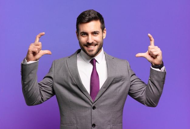Young adult handsome businessman framing or outlining own smile with both hands, looking positive and happy, wellness concept