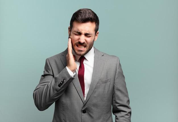 Молодой взрослый красивый бизнесмен, держащий щеку и страдающий от болезненной зубной боли, чувствуя себя больным, несчастным и несчастным, ищет стоматолога