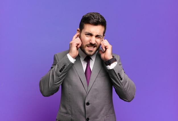 怒り、ストレス、イライラしているように見え、耳をつんざくような音、音、または大音量の音楽で両耳を覆っている若い大人のハンサムなビジネスマン