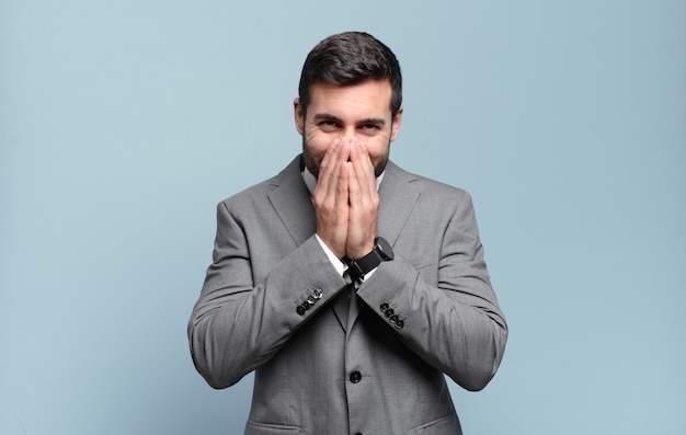 Young adult handsome businessman looking happy, cheerful, lucky and surprised covering mouth with both hands