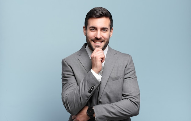 Young adult handsome businessman looking happy